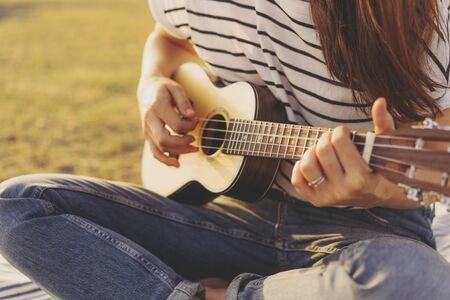 Closeup of female hands playing ukulele guitar, summer mood, sunset soft lighting, joyful entertainment concept of creative leisure