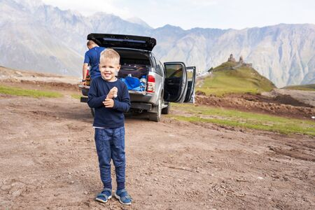Family road trip to Georgia to the ancient monastery of Gergeti, a blond boy close up laughing, lifestyle picture. Stock Photo