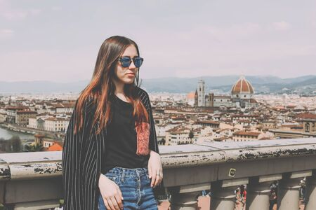 Young pretty female tourist on a viewing platform overlooking the Florence cityscape