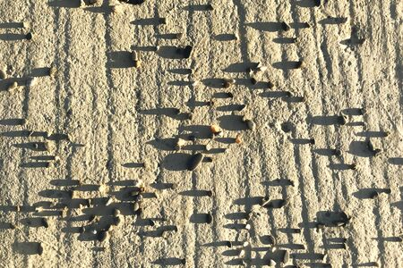 Abstract background, scattered stones on betton surface, long shadow from sunset light.
