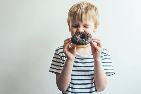 8f06fef0c Child boy closed his eyes and laughs with a chocolate donut in..