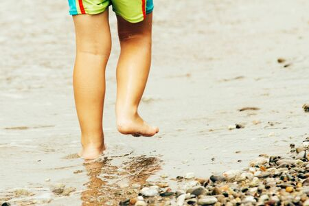 A child in green swimming trunks walks along the water edge along the seashore on a warm summer day, back view.
