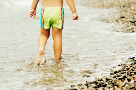 A child in green swimming trunks walks along the water edge along the seashore on a warm summer day, moving away from the viewer from the back to the boy.