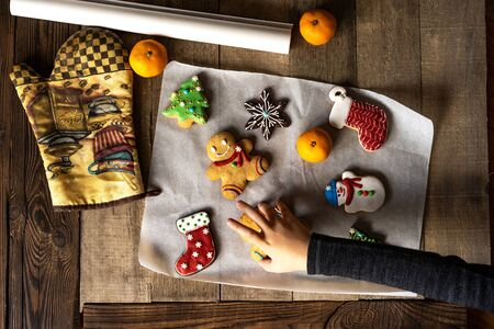 Childrens hand sneaks festive Christmas glazed gingerbread from a wooden table. Stock Photo