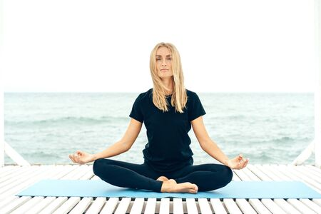 Young authentic woman practices yoga and meditates in the lotus position on the floor of wooden planks on the sea coast. Healthy lifestyle and mental comfort.