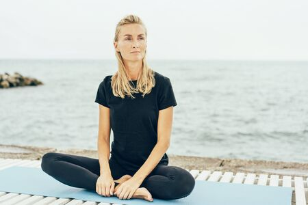 A young slender woman sits in a lotus position after a basic sports training on the bay. Portrait of a beautiful blonde with freckles on her face, natural beauty.