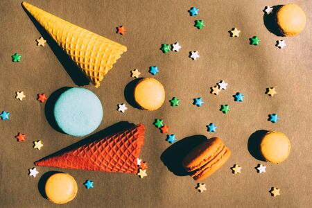 Bright geometric sweets with bright contrasting shadows on a black paper background.