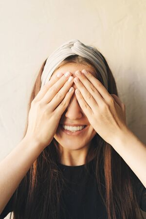 The white young caucasian girl closed her eyes with her hands and showed a charming white-toothed smile. Portrait with a comic gesture. 写真素材