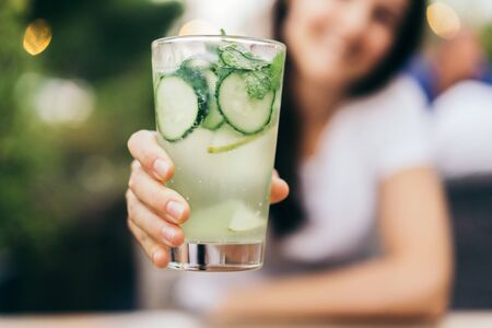 A woman holds out a glass of cucumber lemonade. A cooling non-alcoholic drink on a summer day. Healthy lifestyle.