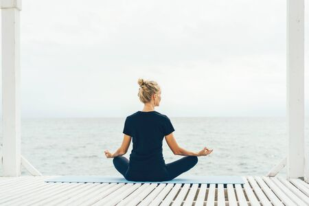 A woman in sportswear is sitting in a lotus position with her back to the camera and meditating while looking at the sea. Calm peaceful mood. Mental comfort.