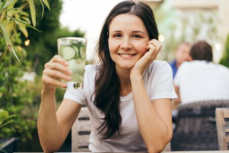 Smiling pleasant young woman holds in her hands a glass with lemonade and ice. Cooling drink in the summer hot season. Healthy lifestyle concept.
