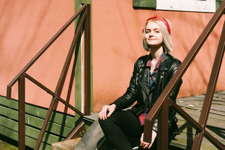 Teenage female hipster in a biker jacket with a hairstyle sits on the steps in front of a house with pink walls. Reklamní fotografie