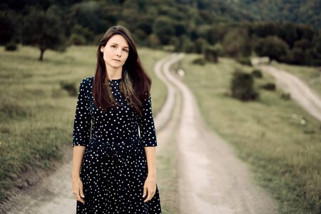 Charming melancholy young �aucasian woman on a background of a country road stretching into the distance.