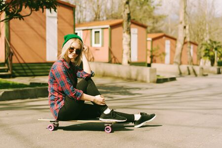 Teenage female hipster in a plaid shirt and a green hat sits on a skateboard on the street with pink camping houses.