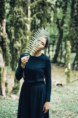 A mysterious woman in a long black dress in the forest covers her face with a fern branch. Fairytale mystic concept. Banco de Imagens