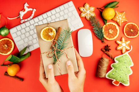 Female hands hold a Christmas gift box in paper packaging with a fir branch and dried orange on a red background with toys and gizmos for decoration and an office keyboard. Corporate New Year party. Banco de Imagens