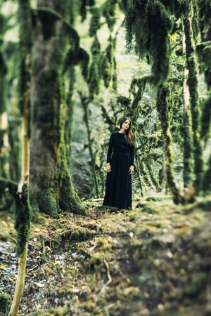 Horror concept for halloween. A girl in a long black dress, like a ghost or a witch, in a mystical spooky forest.