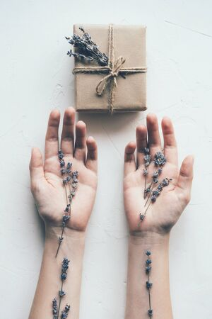 Female hands with palms up on a white background in front of an elegant gift box. Lavender branches cover the skin. Vertical image.