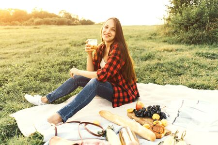 Beautiful caucasian woman with a glass sits on a picnic blanket at sunset.