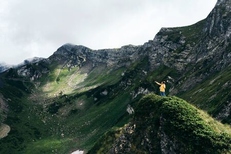A small figure of a woman traveler in a yellow jacket in the mountains. Epic landscape.