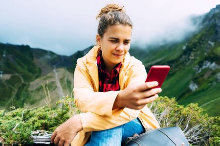 Beautiful caucasian woman reads sms and looks at a mobile phone in the mountains.