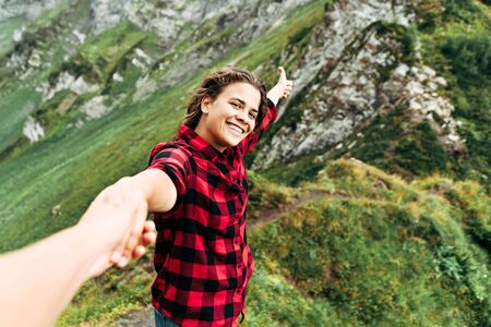 A beautiful Caucasian woman with long curly hair holds the hand of a man and calls for adventures. Follow me concept. Banco de Imagens
