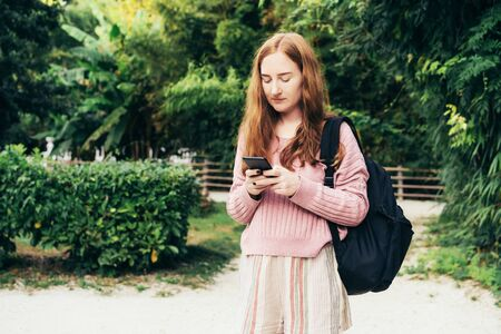 A young Caucasian woman with red hair is holding a phone and typing sms outside.