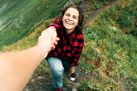 Close-up of a beautiful caucasian curly woman holding the hand of an assistant pulling her to the top of the mountain. Funny happy person in a mountain landscape.