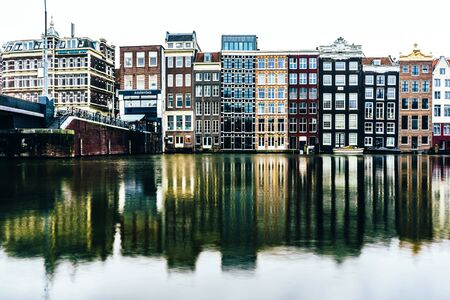 Cityscape with canal and houses in Amsterdam. Water surface with reflections at a long exposure.