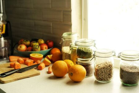 on the table in the kitchen in front of the window are prepared products for freshly squeezed orange and carrot juice.