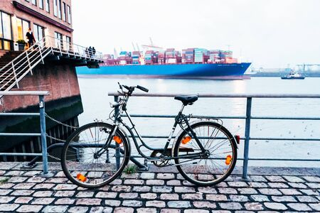 Embankment in the city of Hamburg, close-up of a bicycle on the background of a cargo ship moving in the bay. Banco de Imagens
