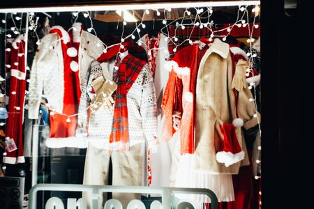 An urban storefront with a warm winter clothing collection on Christmas Eve.