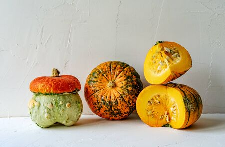 Several unusual ripe pumpkins close-up on a white concrete background. Autumn content. Banco de Imagens