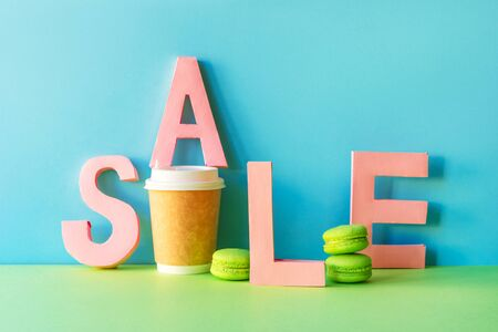 The word SALE is made up of large paper letters. Coffee cup and mint colored macaroons. Paper craft. Banco de Imagens