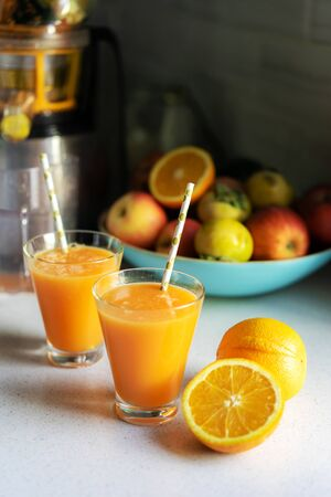On the kitchen table two glasses with freshly squeezed orange juice. Banco de Imagens