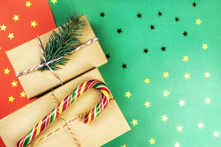 Two Christmas gift boxes decorated with candy cane and fir branch on a two-tone red and green background with confetti in the form of gold stars. A Christmas background with a place for the text.