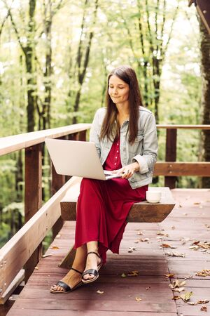 Young caucasian cute brunette woman in a denim jacket and long dress sits on a wooden terrace in the park and looks at information in a laptop. Autumn content. Digital technology concept.