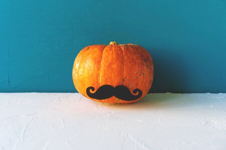 Minimalistic image with one pumpkin with a paper mustache in the center of the frame on a blue background.