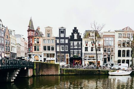Cityscape in Amsterdam. Embankment and traditional buildings along the canal.
