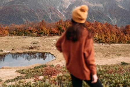 The blurred figure of a woman on a background of mountains. Focus on background.