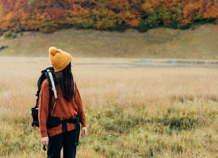 Lonely female person with a hiking backpack in a yellow hat on the background of an autumn landscape with a forest and a lake. Digital detox concept. Copy space.