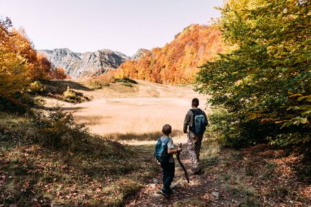 Dad and son walk along a mountain trail in the autumn. Fall mountain landscape.