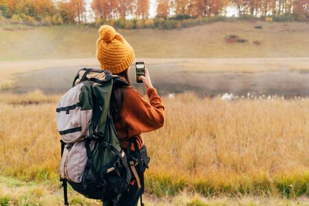 A lonely female person with a hiking backpack in a yellow hat takes a photo of the autumn landscape with a forest and a lake. Digital detox concept. Copy space.