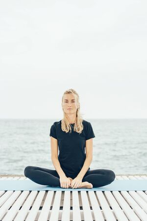 Young pleasant caucasian woman in sportswear is sitting in lotus position after exercise outdoors.