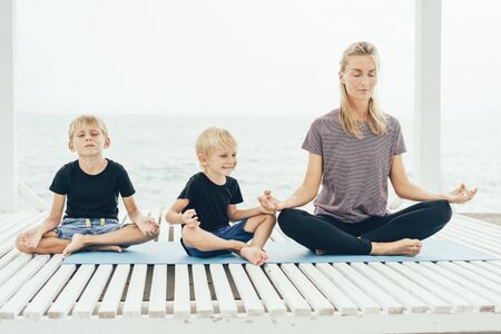 Young caucasian mother with two sons practices yoga outdoors on the seashore. Family care for mental and physical health. The concept of a healthy lifestyle and close trusting relationships. Banco de Imagens