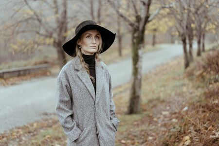 Young caucasian woman in a hat and a gray coat in the rain against the backdrop of an autumn landscape. Pensive melancholy autumn mood.