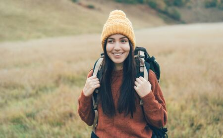 Portrait of a young activist female athlete tourist traveler with a heavy backpack on her back. Cute white brunette woman in a yellow knitted hat smiles against the backdrop of an autumn landscape.