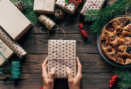 Top view of a wooden surface on which lie gift boxes and fir branches. Female hands hold one gift in polka dot wrapping paper. Cute Christmas flat lay. Festive concept. Banco de Imagens