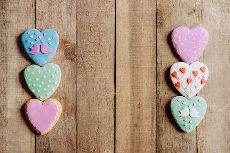Concept for Valentines Day greetings. Gingerbread glazed cookie hearts on a rustic wooden background. Festive lovely concept.