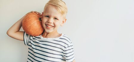 Blond funny Caucasian boy in a striped T-shirt jokes with a ripe pumpkin. Cheerful portrait of a child. Copy space for text. Halloween content.